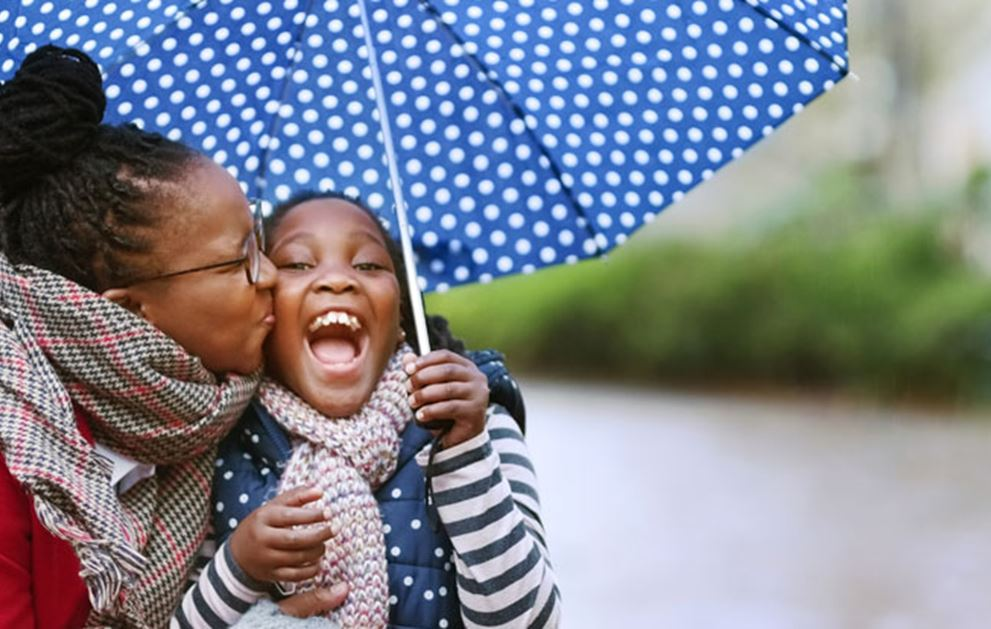 Mom and daughter laughing in the rain